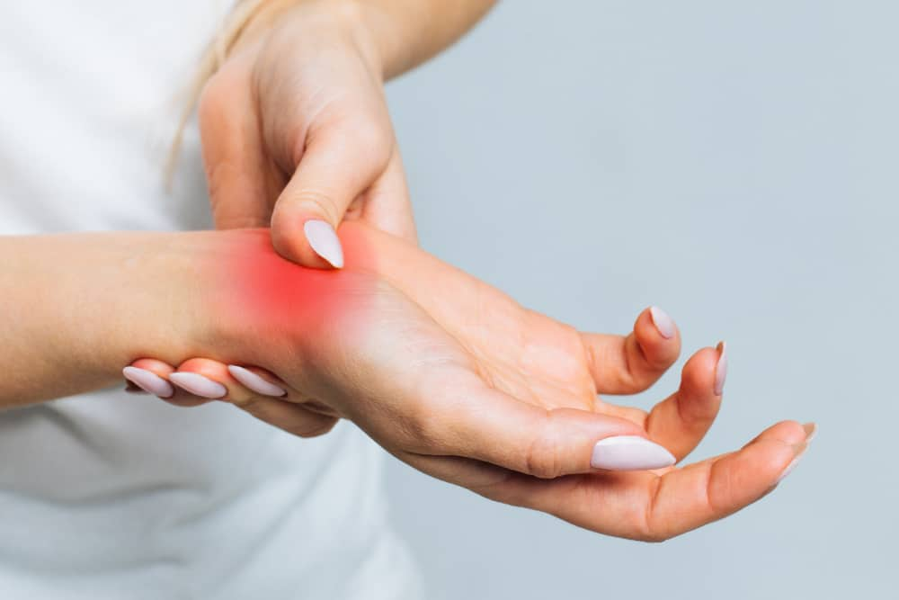 woman holding painful wrist caused by prolonged work computer carpal tunnel syndrome arthritis
